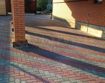 Участок около дома мощенный тротуарной плиткой волна с сочетанием цветов серый и красный