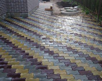 Площадка около дома мощенная тротуарной плиткой волна из цветовых гам серый, желтый и коричневый
