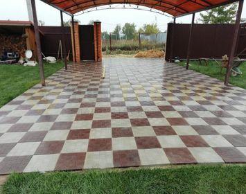 Площадка под легковую машину на даче мощенная тротуарной плиткой паркет из серого и коричневого цвета в шахматном порядке