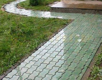 Дорожка на дачном участке мощенный тротуарной плиткой волна серого цвета