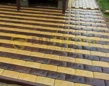 Участок около дома мощенная тротуарной плиткой Английский булыжник, желтого и коричневого цвета
