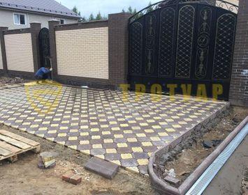 Площадка под машину мощенная тротуарной плиткой краковский клевер с сочетанием цветов желтый и коричневый