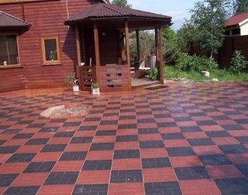 Площадка возле дома мощенная тротуарной плиткой 8 кирпичей сочетанием цветов красный и черный в шахматном порядке