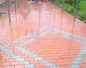 Площадка на дачном участке мощенная тротуарной плиткой волна красного и серого цвета